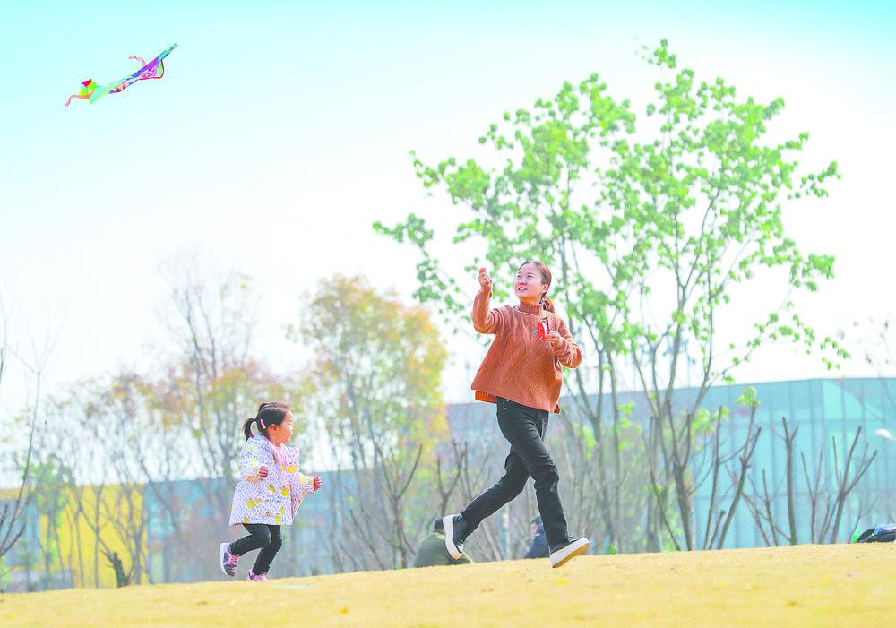 公园里和孩子一起放飞风筝的市民