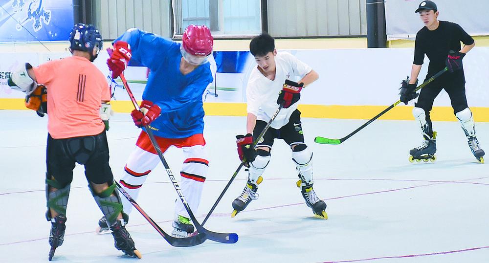 在轮滑冰球馆内,爱好者们进行冰球比赛 图据新华社